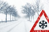 Snowfall on a country road with traffic sign