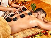 picture of stone-therapy  - Man getting stone therapy massage in bamboo spa - JPG