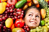 Young woman in group of fruit. Healthcare.