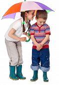 Two little children under umbrella