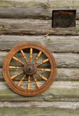 Hand Spinning Wheel On The Log House Wall
