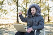 Cheerful young man in fur hood jacket using laptop in the forest on a winter day