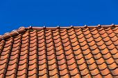picture of red roof tile  - Red roof tile pattern over blue sky - JPG
