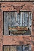 picture of yesteryear  - The rusty silhouette of a western steer head is nailed to the weathered door of a shed with a rusted out metal container nailed below it in an artistic garden art collage - JPG