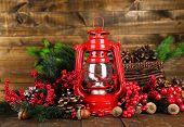 Red kerosene lamp on wooden table on wooden background