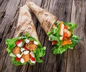 Chicken strips in a Tortilla Wrap with Lettuce on wood.