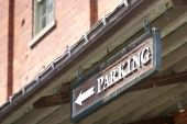Custom Parking Sign With Arrow On Side Of Building