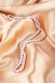 Beautiful pearls on golden silk cloth