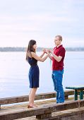 Young Interracial Couple Holding Hands Standing On Dock Over Lake