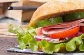 Sandwich With Ham And Vegetables On A Background Of Books