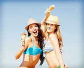 summer holidays and vacation concept - girls in bikini with ice cream on the beach