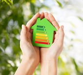 energy saving, real estate and family home concept - closeup of female hands holding green paper hou