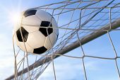 stock photo of football  - Football or soccer goal with a neutral design ball flying into the net blue sky and sun in the background - JPG