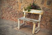 stock photo of quaint  - Empty Rustic wooden outdoor cottage bench painted white against wall - JPG