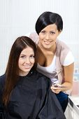 Half-length portrait of hairdresser and the client sitting on the chair. Concept of stylish haircut
