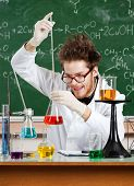 pic of mad scientist  - Mad professor adds something to the Erlenmeyer flask with red water - JPG