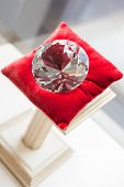 Close up of large diamond on red pillow at jeweler's shop. Concept of wealth and luxurious life
