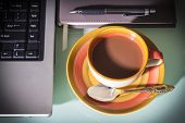 Coffee Cup With Laptop And Pen On Notebook