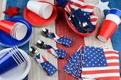 HIgh angle photo of a picnic table setting for a Fourth of July party. Plates, cups, napkins, and ot