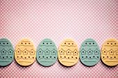Decorated felt easter eggs yellow and blue on a pinky polka dots background.  Vintage style.