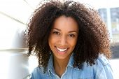 stock photo of cheer-up  - Close up portrait of a cheerful young african american woman smiling outdoors - JPG