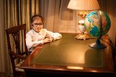 Little Girl In Eyeglasses Sitting Behind Desk