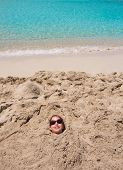 Funny kid girl playing buried in beach sand smiling with sunglasses at summer vacation