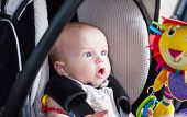 stock photo of stare  - baby boy in car seat stares at the toy - JPG