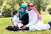 cheerful muslim family sitting outdoors