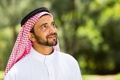 handsome middle eastern man looking up outdoors