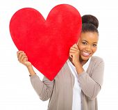 portrait of happy african woman holding red heart symbol