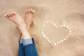 image of wet feet  - Female feet closeup of woman standing at the sandy beach next to the shell heart - JPG