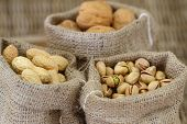 Walnuts, pistachio nuts and peanuts in jute bags