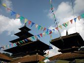 stock photo of nepali  - Traditional Nepali Prayer Flags in front of a temple complex in the ancient king city of Patan near Kathmandu Nepal.