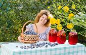 Woman with  compote of plums in the garden