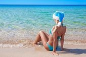 Beautiful Blonde Woman In Blue Christmas Hat On Sea Beach.
