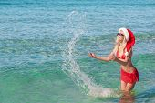 Beautiful Blonde Woman In Red Christmas Hat On Sea Beach Making