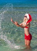 Beautiful Blonde Woman In Red Christmas Hat On Sea Beach Making water splashes.