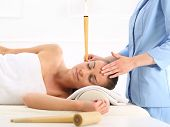 pic of ear candle  - Woman relaxes in the study of natural medicine - JPG