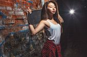 stock photo of skate board  - Beautiful Asian teen girl with skate board on shoulders. Outdoors, urban lifestyle. ** Note: Soft Focus at 100%, best at smaller sizes - JPG