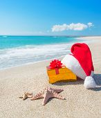 Santa Claus Hat And Christmas Gift Box On Sea Beach