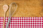 Wooden background with whisk and wooden spoon