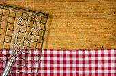Wooden background with whisk and cooling rack