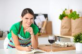 Happy beautiful woman standing in her kitchen writing on a notebook at home