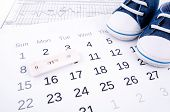 picture of family planning  - Positive pregnancy test on calendar and baby shoes - JPG
