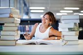 female teenager student sitting with big piles of book smiling