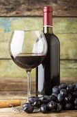 Winery Background. Dark Blue Grapes With Bottle Of Red Wine