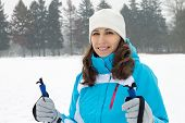 Young Smiling Woman Skiing On Winter Meadow