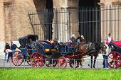 Coachmen Sitting On Chairs, Pulled By A Horse, Waiting For Tourists To The Area Near The Colosseum I