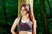 Relaxing runner resting and listening to music on headphones in forest after training